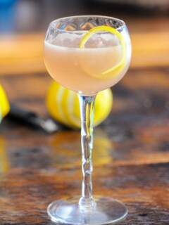 Pink cocktail in coupe with lemon peel