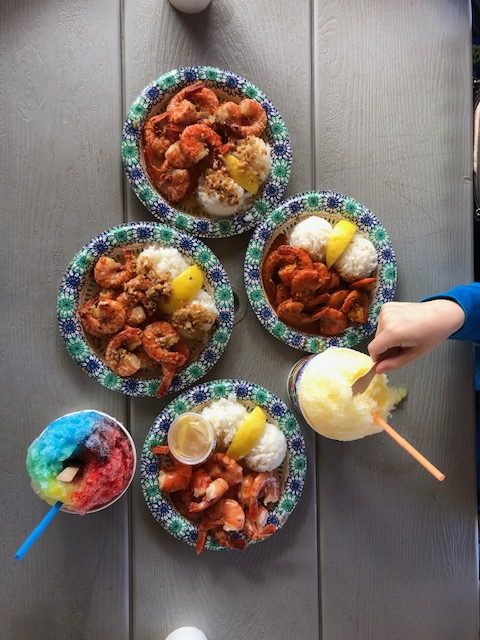 Hand reaching for shave ice and plates of shrimp