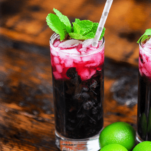 Blueberry Non Alcoholic Mojito, red cocktails in tall glass with mint, silver dot straw, limes