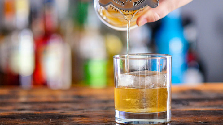 Rye Old Fashioned being poured into rocks glass from mixing glass
