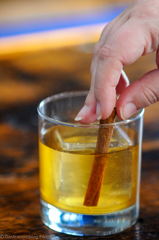 cinnamon stick being placed into a rocks glass with ice