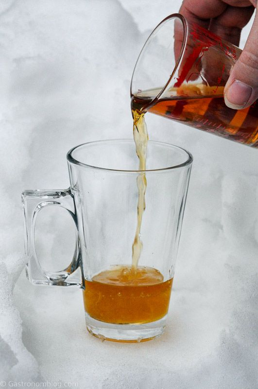 Cognac being poured into glass mug with handle in the snow