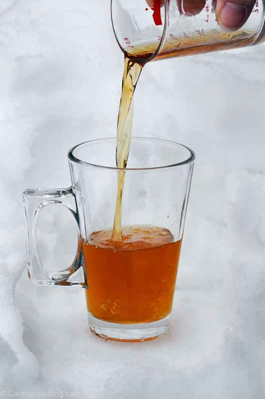 Cognac toddy in glass mug with handle, honey and juice being poured into it