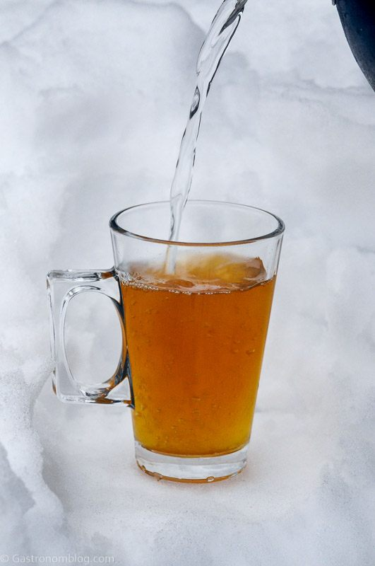Hot water being poured into glass mug with handle in the snow