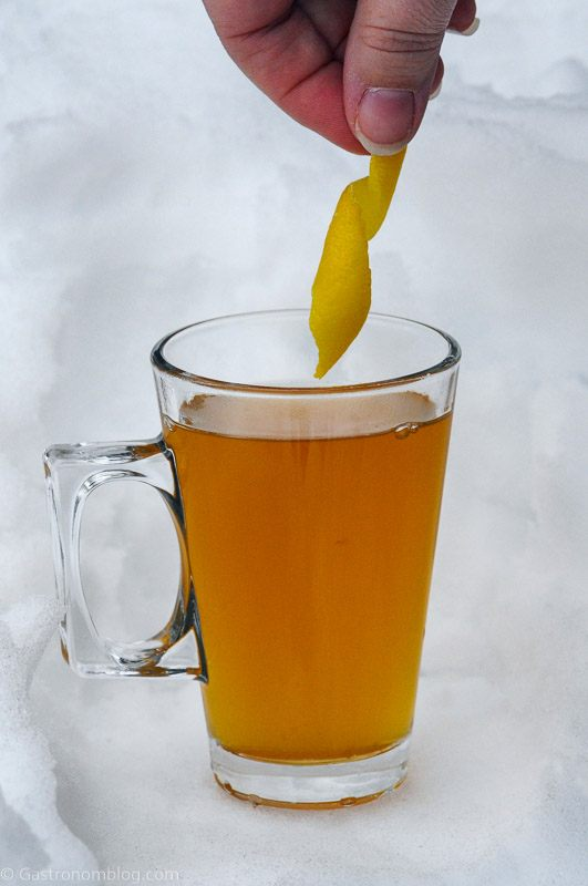 Lemon peel being placed into cognac toddy in glass mug in the snow
