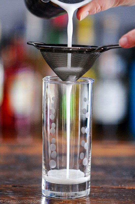 Cocktail being poured into tall glass from shaker through a mesh strainer