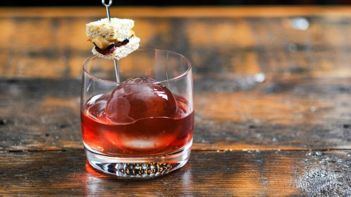Pink cocktail in rocks glass with clear ice ball, tiny peanut butter and jelly sandwich