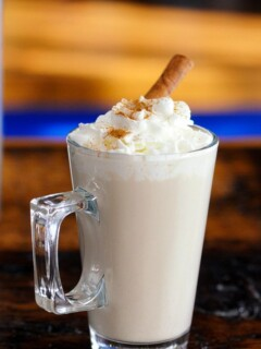 Coffee cocktail in glass mug with whipped cream and cinnamon stick