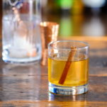 cocktail with cinnamon stick and clear ice in rocks glass, mixing glass behind