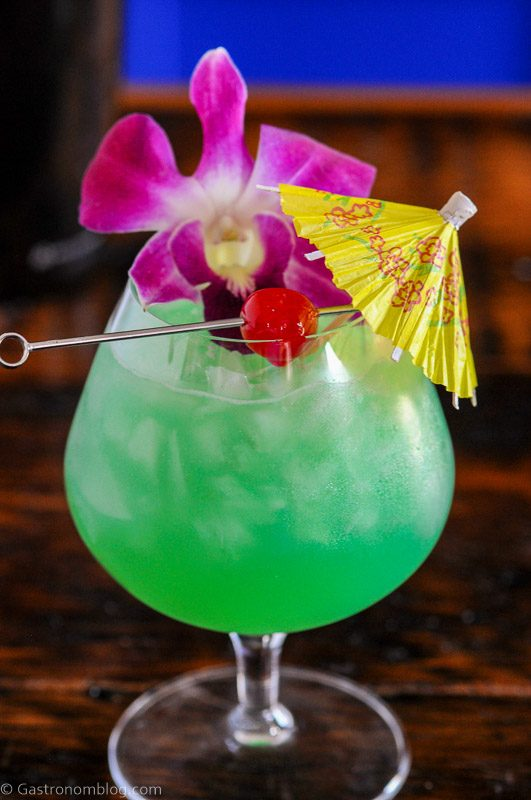 Blue green cocktail in balloon glass with crushed ice, paper umbrella, cherry and orchids