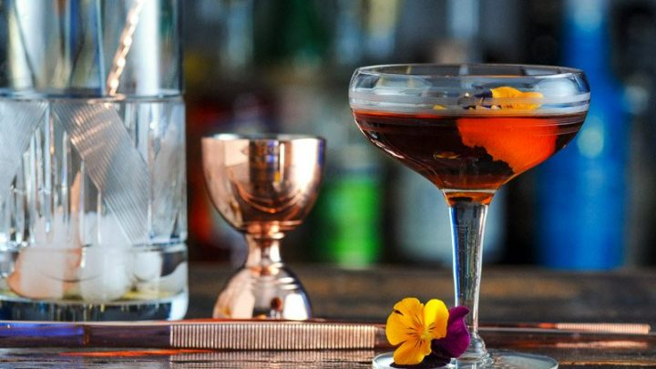 Brown cocktail in coupe, brass jigger and mixing glass behind