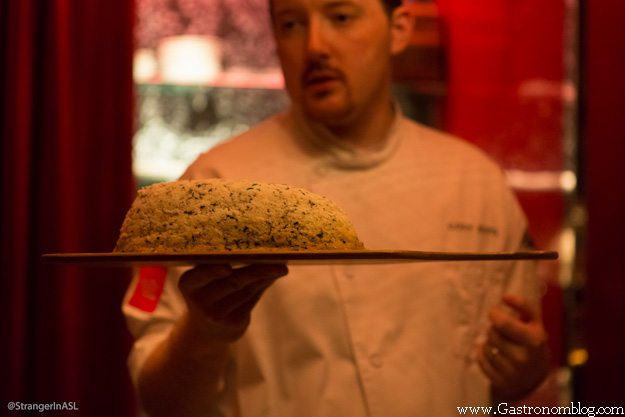 Chef holding board of foie gras baked in salt
