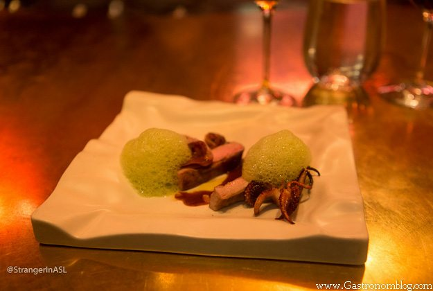 Pork with squid, green foam on white plate at e by Jose Andres