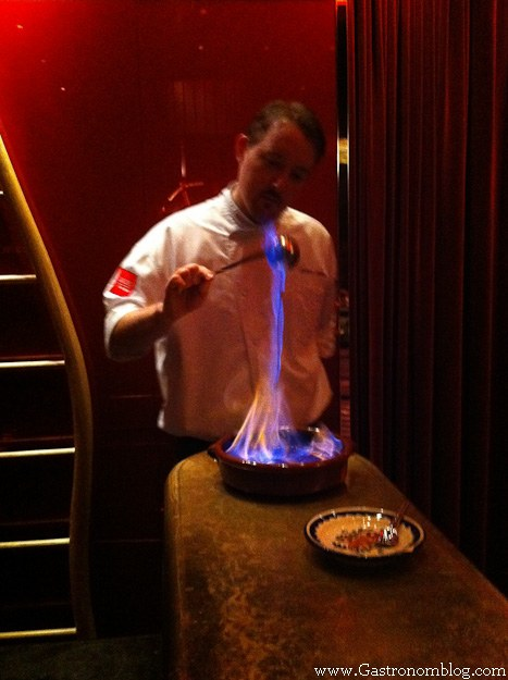 Chef lighting a course on fire for dinner at e by Jose Andres
