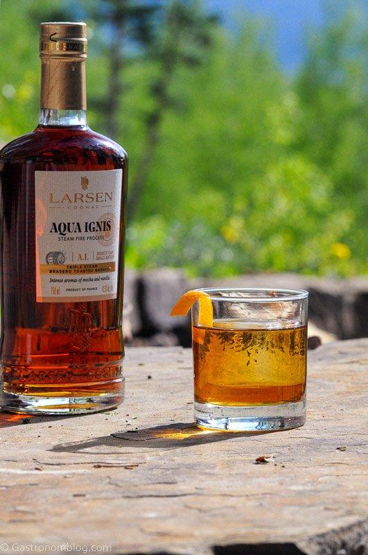 Cognac Old Fashioned in rocks glass with orange peel, cognac bottle behind