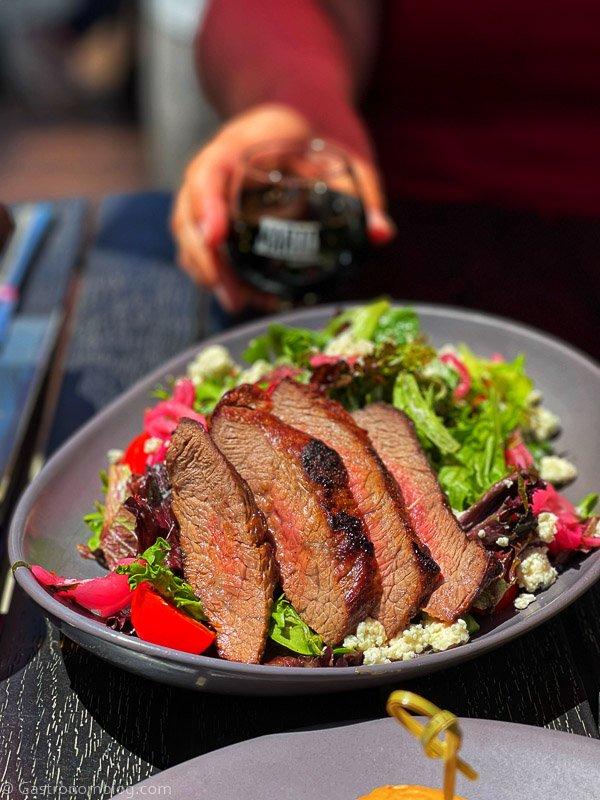 Steak salad in bowl, hand holding beer behind