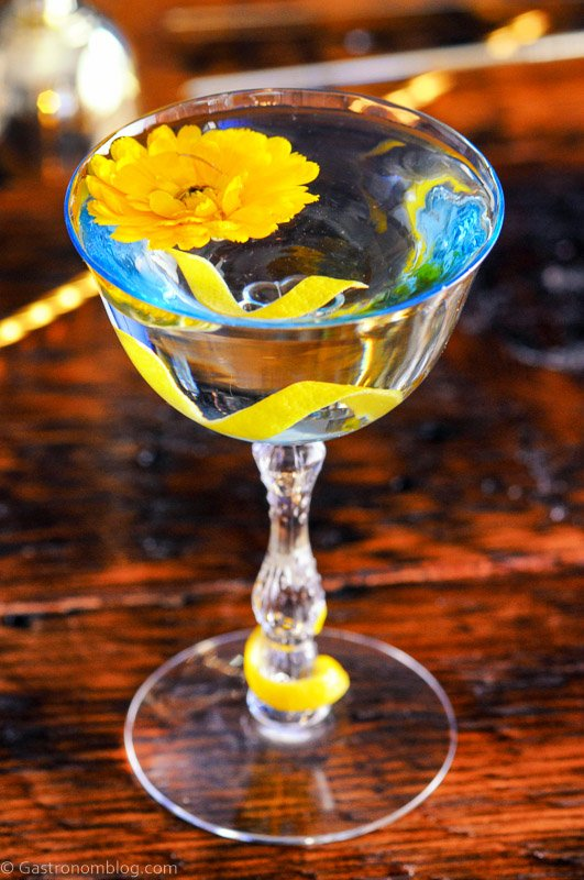 El Presidente Cocktail in blue tinted coupe, lemon peel and yellow flower on top