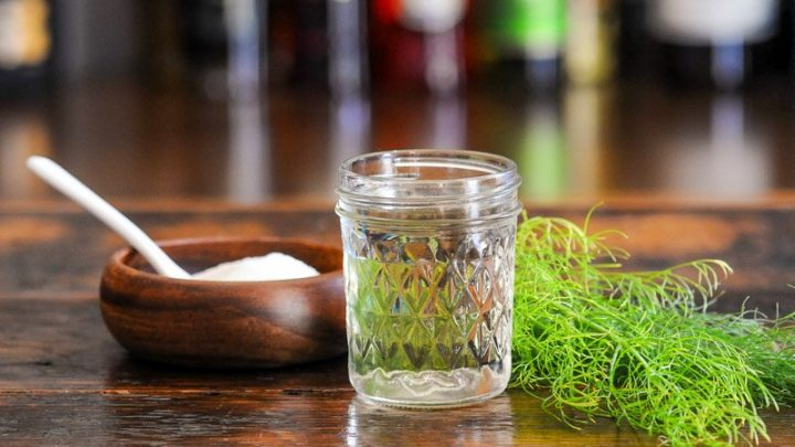 syrup in jar with fennel fronds, wooden bowl of sugar
