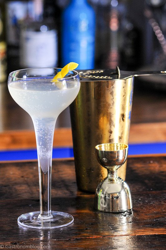 French 75 cocktail in coupe with lemon peel and gold bar tools