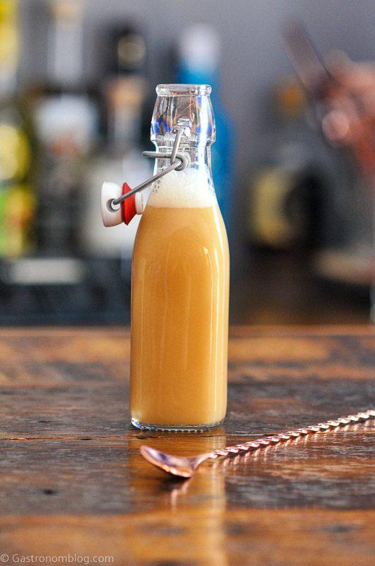 Tan liquid in bottle, gold spoon on wood table