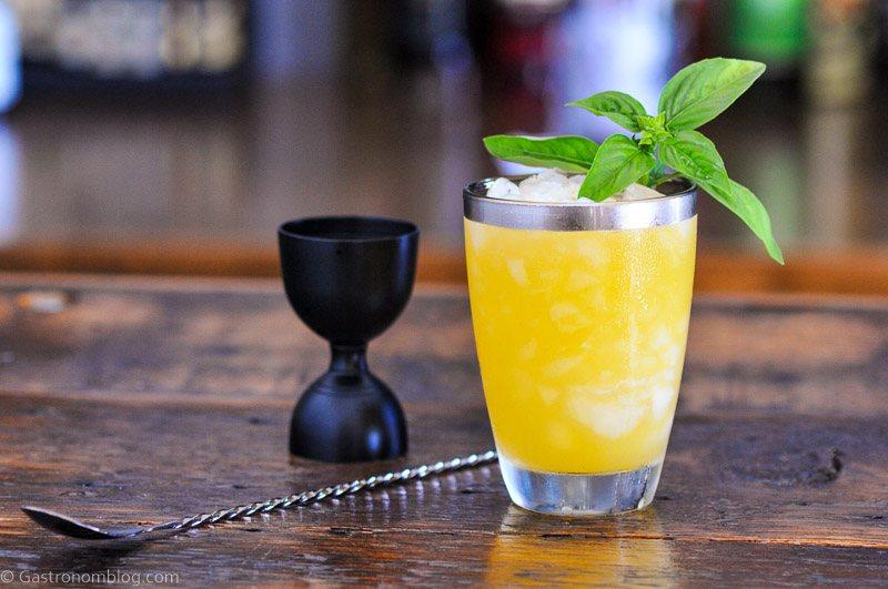 Peach basil gin smash cocktail, orange cocktail in silver rimmed glass, black barspoon and jigger, basil as garnish