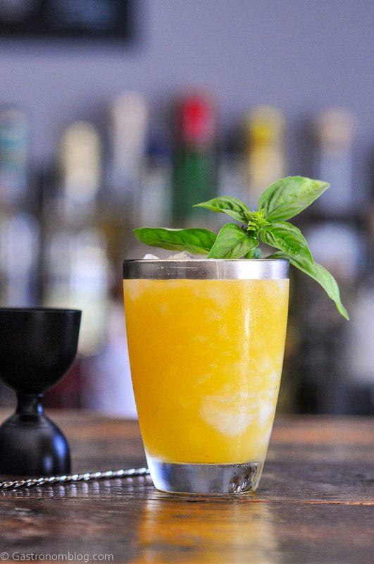 Orange cocktail in silver rimmed glass, basil leaves on top, black jigger