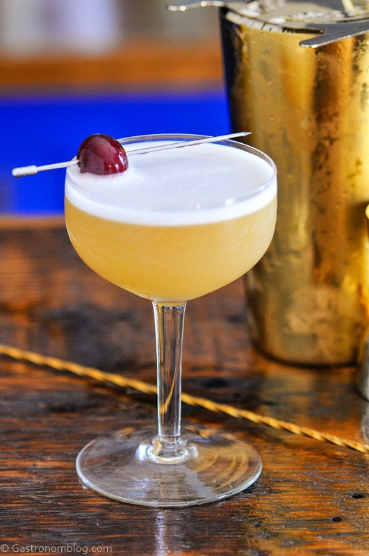 Peach Bourbon Sour, yellow cocktail with white foam in cocktail coupe, cherry on pick. Gold Barware behind