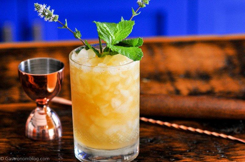 Orange cocktail in double rocks glass, mint leaves, brass barware behind