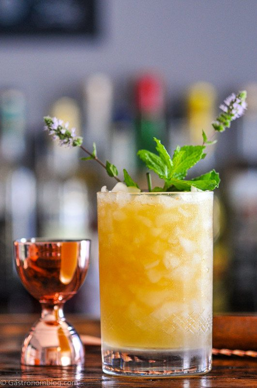 Peach Whiskey Smash Cocktail, orange in double rocks glass with crushed ice and mint leaves, brass barware behind
