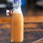 DIY Caramel Vodka, tan liquid in bottle, gold spoon