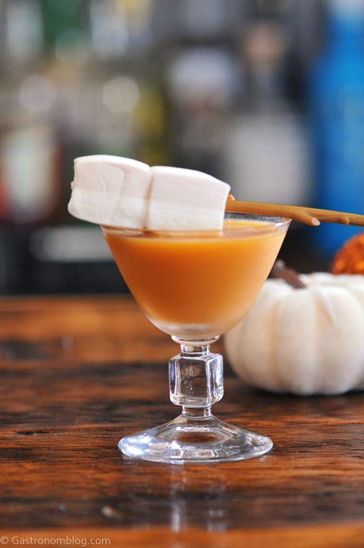 Orange cocktail in glass, marshmallows on stick as garnish. Pumpkins behind