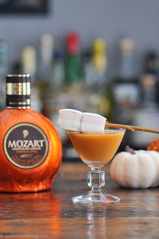 Pumpkin Salted Caramel Martini in coupe, marshmallows on stick garnish, orange liqueur bottle behind